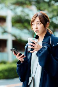 アイスコーヒーを飲みながらスマートフォンをチェックする若い女性の写真素材 [FYI01823216]