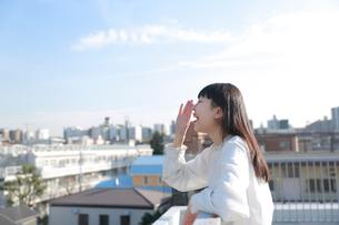 屋上で手を口の前に添えて叫ぶ女性の写真素材 [FYI01823238]