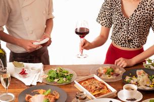 イタリアンのコース料理と赤ワインを楽しむ女性とソムリエの写真素材 [FYI01823257]