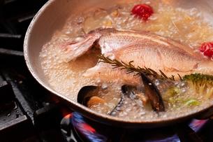 魚丸ごとアクアパッツァ調理中の写真素材 [FYI01823323]