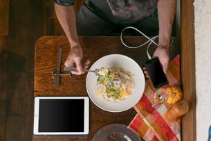 スマホを持ちながら食事風景の写真素材 [FYI01823356]