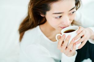 温かい飲み物を飲む女性の写真素材 [FYI01823387]