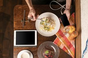 スマホを持ちながら食事風景の写真素材 [FYI01823391]