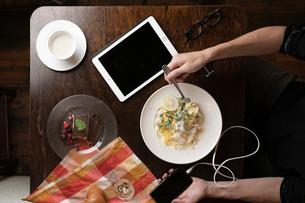 スマホを持ちながら食事風景の写真素材 [FYI01823397]