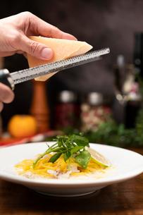 チーズを削ってしまなみレモンのクリームパスタに投下の写真素材 [FYI01823413]