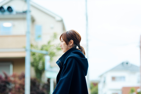 街中で立ち止まる若い女性の写真素材 [FYI01823445]
