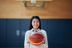 体育館でバスケットボールを持つ女子高生の写真素材 [FYI01823482]