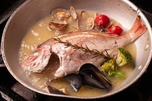 魚丸ごとアクアパッツァ調理中の写真素材 [FYI01823887]