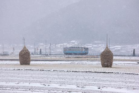 雪の宇和盆地を走る列車の写真素材 [FYI01824583]