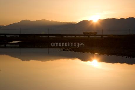 石鎚山と鉄橋を渡るローカル列車と朝日の写真素材 [FYI01824725]
