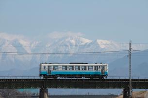 ローカル列車と雪の石鎚連山の写真素材 [FYI01824830]