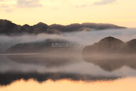 水面に映る朝焼けと朝霧の写真素材 [FYI01824922]