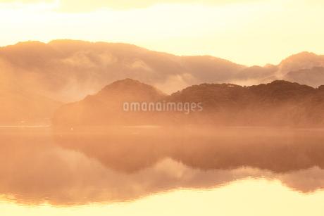 水面に映る朝焼けと朝霧の写真素材 [FYI01825242]