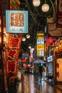 雨降る夜に中野の路地を歩く人たちの写真素材 [FYI01826334]