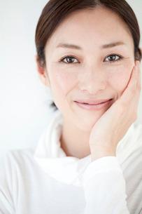 片手をほほにあて微笑む中年女性の写真素材 [FYI01826401]