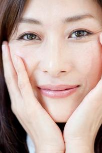 両手をほほにあて微笑む中年女性の写真素材 [FYI01826437]