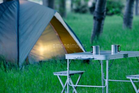 早朝のキャンプ場にテントとマグカップ二つの写真素材 [FYI01826458]