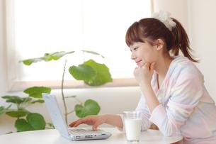 部屋着でパソコンをする若い女性の写真素材 [FYI01826489]