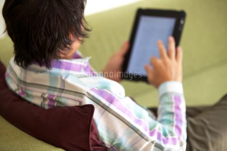 リビングでタブレットPCをする中年男性の写真素材 [FYI01826501]