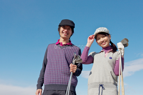 青空バックでゴルフクラブを持って微笑むカップルの写真素材 [FYI01826676]