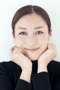 あごに両手をあてて微笑む中年女性の写真素材 [FYI01826743]