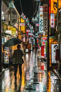 雨降る夜に中野の路地を歩く人たちの写真素材 [FYI01826924]