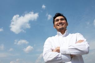 白いシャツで笑う男性青空バックの写真素材 [FYI01827009]