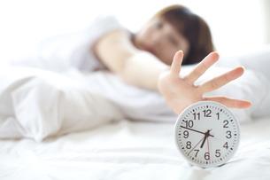 目覚まし時計を止めようとしている20代女性の写真素材 [FYI01827012]