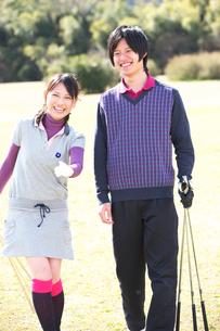 ゴルフクラブを持ってグリーンで指さす若いカップルの写真素材 [FYI01827113]
