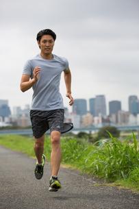 都会をバックにジョギングする20代男性の写真素材 [FYI01827147]