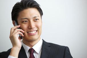 電話を掛ける20代ビジネスマンの写真素材 [FYI01827247]