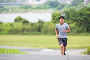 上り坂をジョギングする20代男性の写真素材 [FYI01827376]