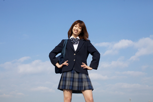 青空バックに両手を腰にあて笑顔の女学生の写真素材 [FYI01827427]
