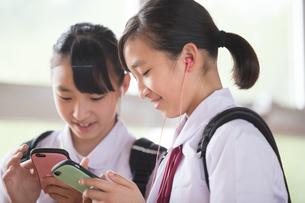 スマートフォンで音楽を聞く双子の女子中学生の写真素材 [FYI01827790]