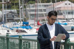 水辺に立ちタブレットを持つ30代男性クリエイターの写真素材 [FYI01827840]
