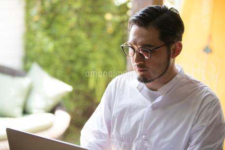 ノートパソコンで作業する30代男性クリエイターの写真素材 [FYI01827845]