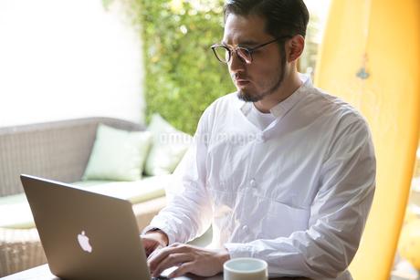ノートパソコンで作業する30代男性クリエイターの写真素材 [FYI01827853]