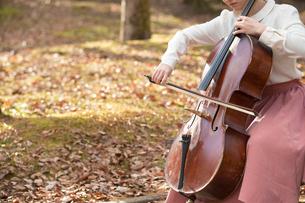 公園でチェロを弾く20代女性の写真素材 [FYI01827856]