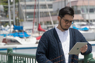 水辺に立ちタブレットを持つ30代男性クリエイターの写真素材 [FYI01827898]