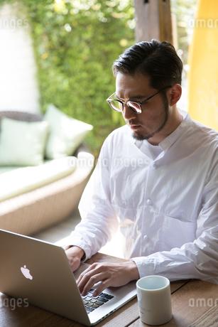ノートパソコンで作業する30代男性クリエイターの写真素材 [FYI01827908]