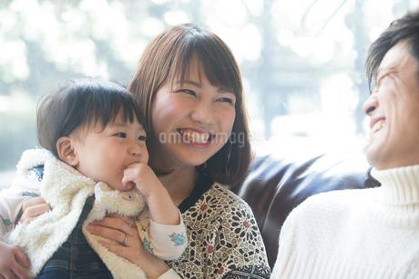 笑顔でポーズする20代夫婦と子供の写真素材 [FYI01827983]