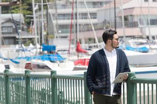 水辺に立ちタブレットを持つ30代男性クリエイターの写真素材 [FYI01828003]