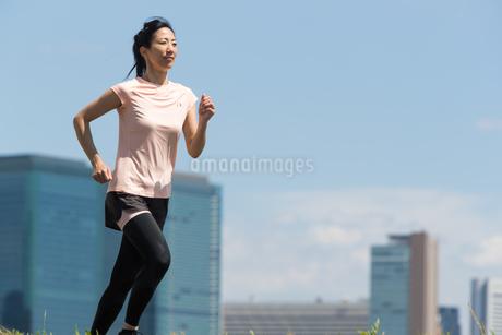 都会バックにジョギングする40代女性の写真素材 [FYI01828097]