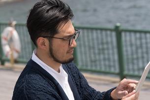 水辺に立ちタブレットを持つ30代男性クリエイターの写真素材 [FYI01828156]