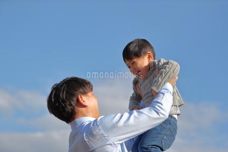 子供を高く抱き上げる父親の写真素材 [FYI01828248]