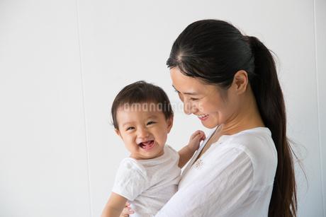 白バックの前で微笑む20代母と赤ちゃんの写真素材 [FYI01828390]