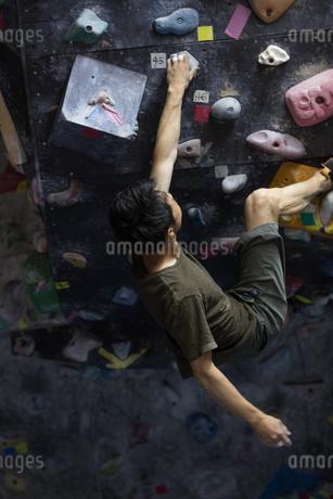 ボルダリングする30代男性の写真素材 [FYI01828639]