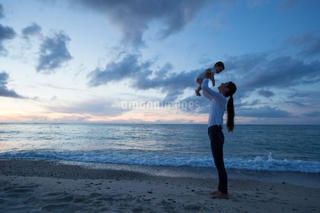 ビーチで微笑む20代母と赤ちゃんの写真素材 [FYI01828670]