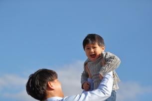 子供を高く抱き上げる父親の写真素材 [FYI01828697]