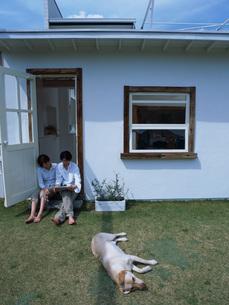 寝転ぶ犬とカップルの写真素材 [FYI01829253]